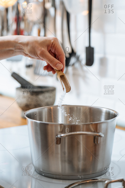 Woman sprinkling salt into water in pot on stove