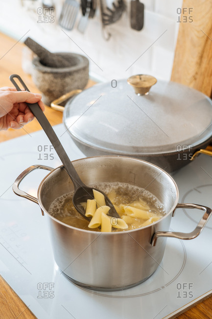 Woman stirring noodles in pot on stove