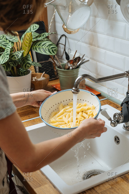 Woman rinsing noodles in a colander in a sink
