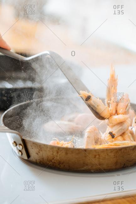 Woman stirring prawns in a skillet