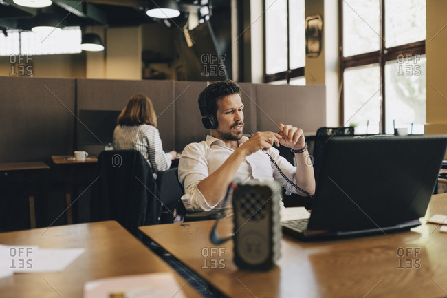Creative businessman wearing headphones while video conferencing on laptop in office