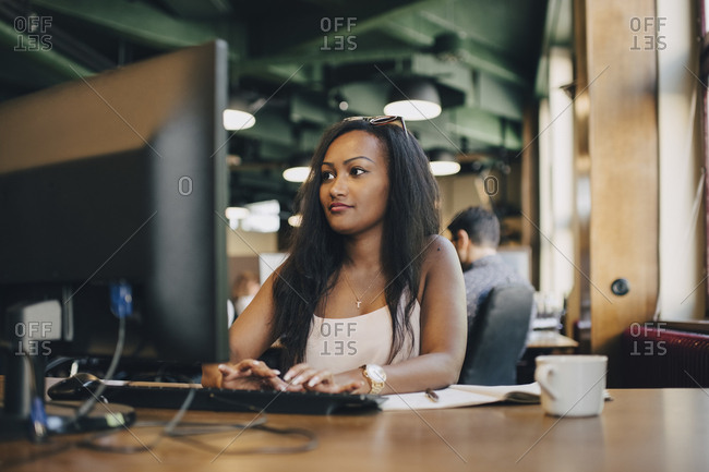 Young businesswoman using computer at desk in creative office