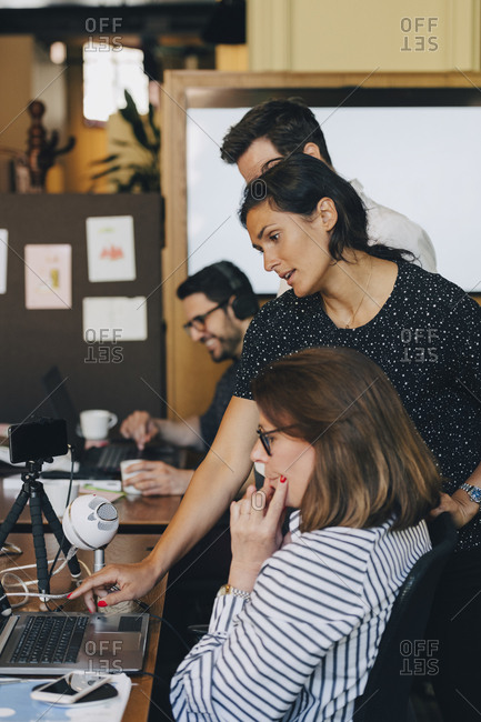 Mid adult businesswoman discussing with team over laptop in office