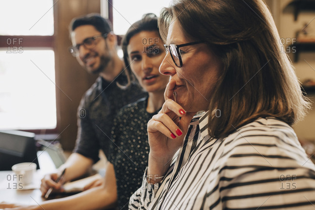 Thoughtful mature businesswoman by colleagues during discussion in office
