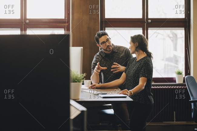 Mid adult businessman discussing new plan with female colleague in office