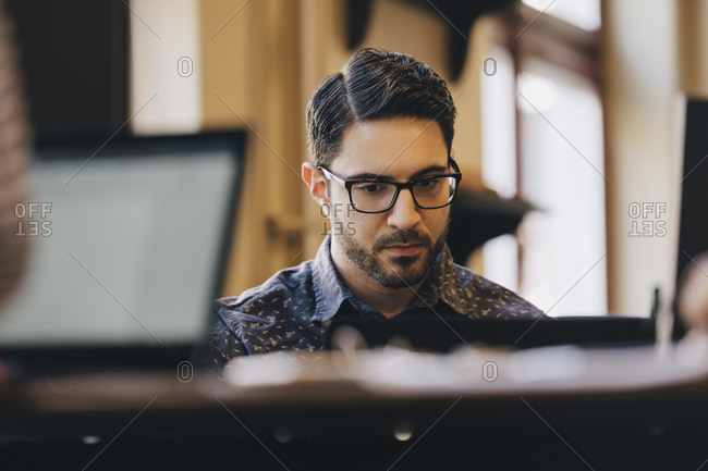 Businessman wearing glasses while working in creative office