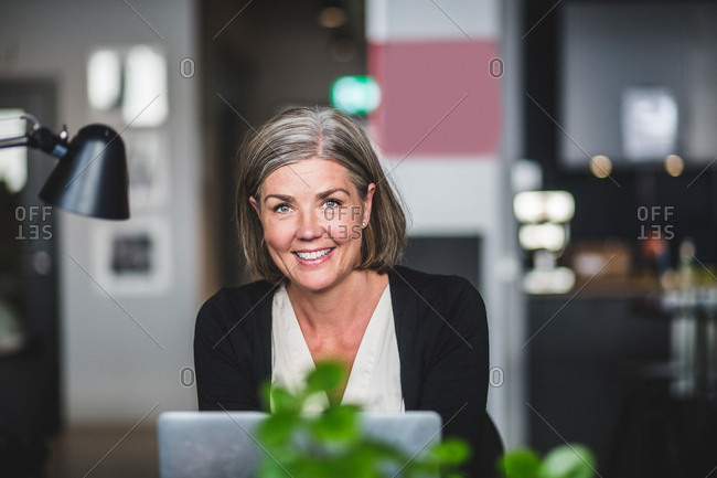 Portrait of confident businesswoman sitting at desk in creative office