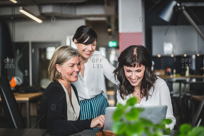 Creative businesswomen smiling while discussing over laptop at desk in office