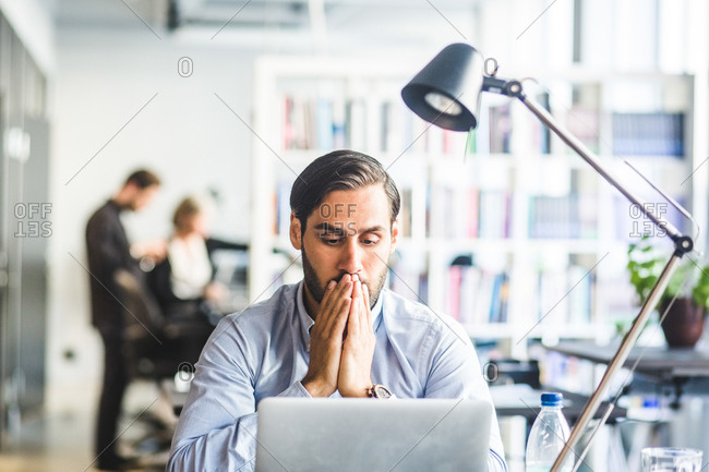 Tensed businessman covering mouth while looking at laptop in office