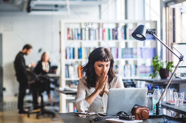 Worried businesswoman with hands clasped looking at laptop while sitting in office