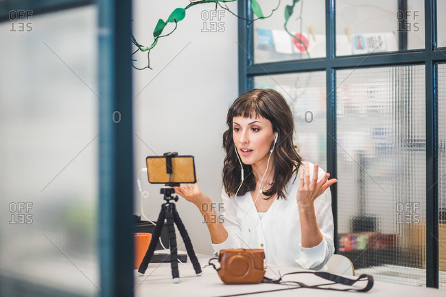 Creative businesswoman attending video conference through mobile phone at desk in office