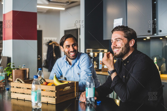 Male colleagues smiling while sitting at table in office