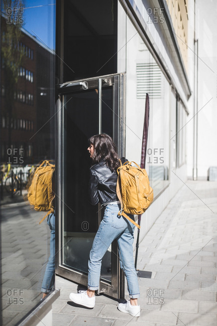 Businesswoman with backpack opening door at entrance of office
