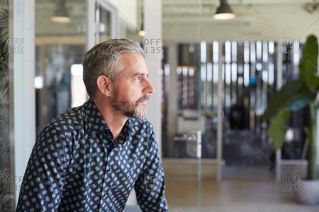 Thoughtful mature businessman looking away while sitting in creative office