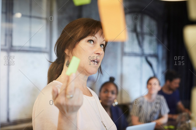 Businesswoman discussing ideas with colleagues over adhesive notes in board room