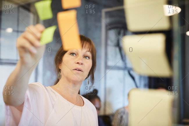 Mature businesswoman sticking sticky note on glass in creative office
