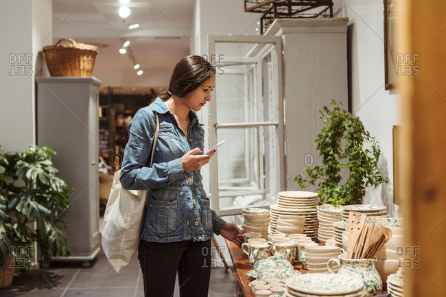 Young woman with mobile phone choosing crockery arranged on table in boutique