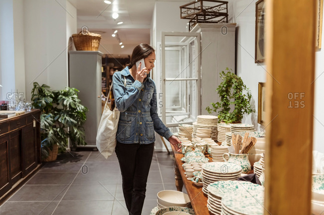 Young woman talking on mobile phone while looking at crockery arranged on table in store