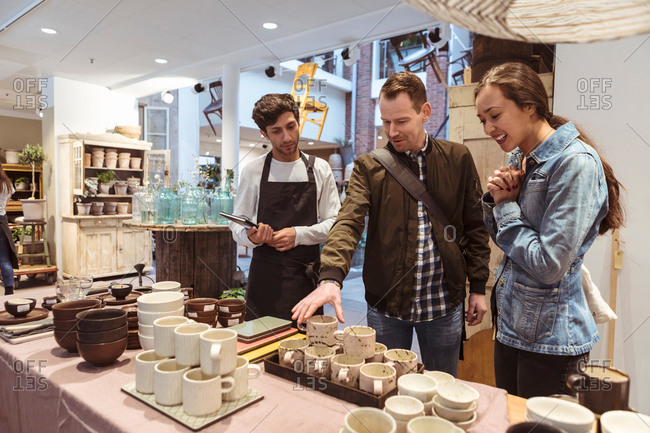 Salesman assisting couple in buying crockery at boutique