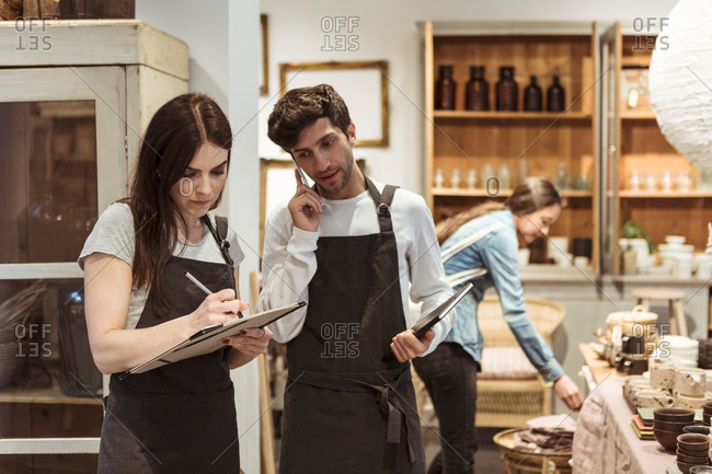 Male entrepreneur using phone while looking at female colleague writing on clipboard in boutique