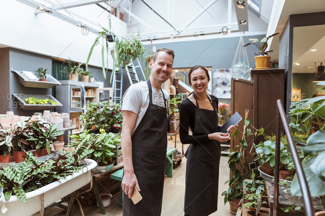 Portrait of male and female partners with digital tablet by plants at store