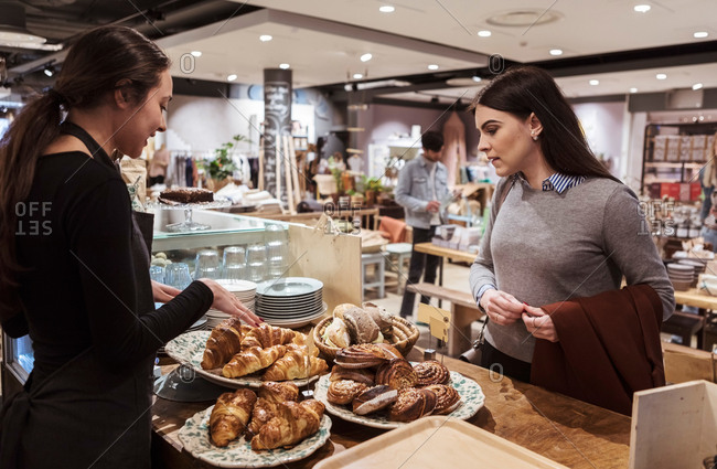Saleswoman showing baked food to female customer at cafe