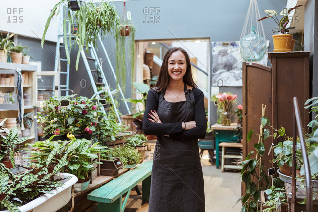 Portrait of smiling female owner standing with arms crossed by potted plants at store
