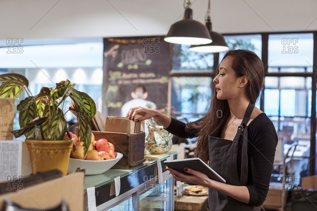 Young saleswoman holding digital tablet while analyzing merchandise at cafe