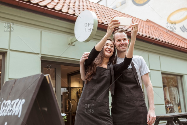 Smiling male and female colleagues taking selfie through mobile phone outside boutique