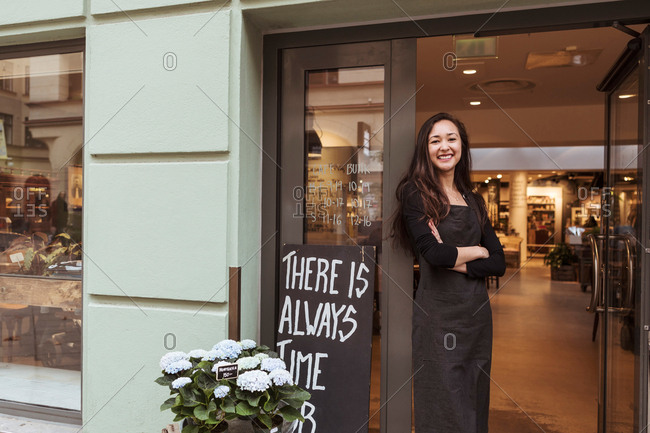 Portrait of smiling saleswoman standing at doorway in boutique
