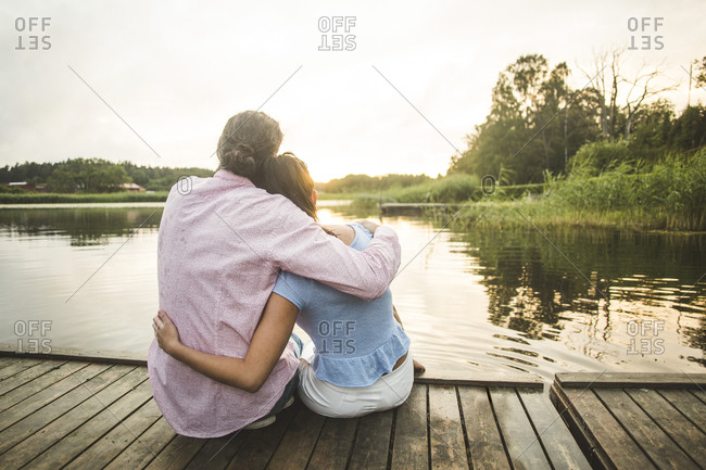 Rear view of couple sitting with arms around on jetty over lake during sunset