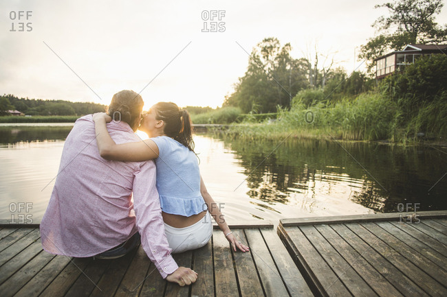 Rear view of boyfriend kissing girlfriend sitting with arms around on jetty over lake during sunset