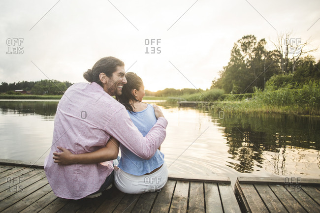 Rear view of smiling couple sitting with arms around on jetty over lake during sunset