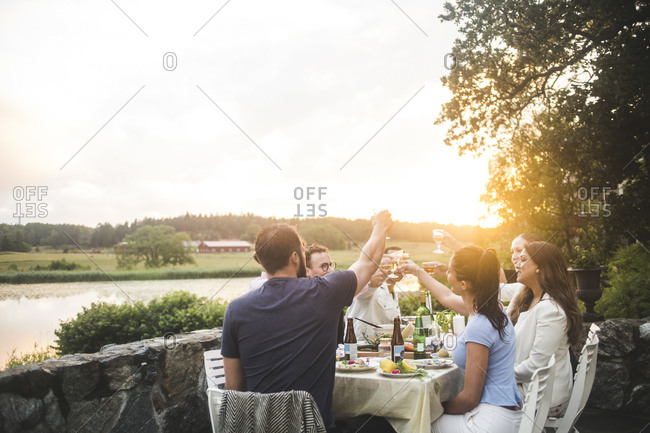 Male and female friends toasting drinks at dining table against sky during sunset