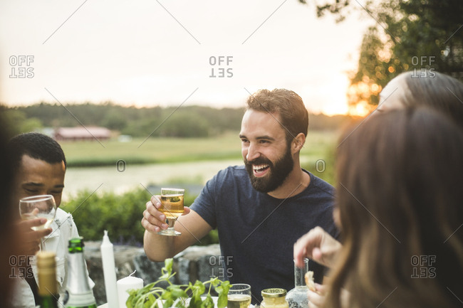 Cheerful male and female friends enjoying drink dinner in backyard during sunset
