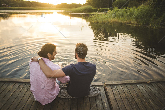 Rear view of smiling male friends sitting on jetty over lake during weekend