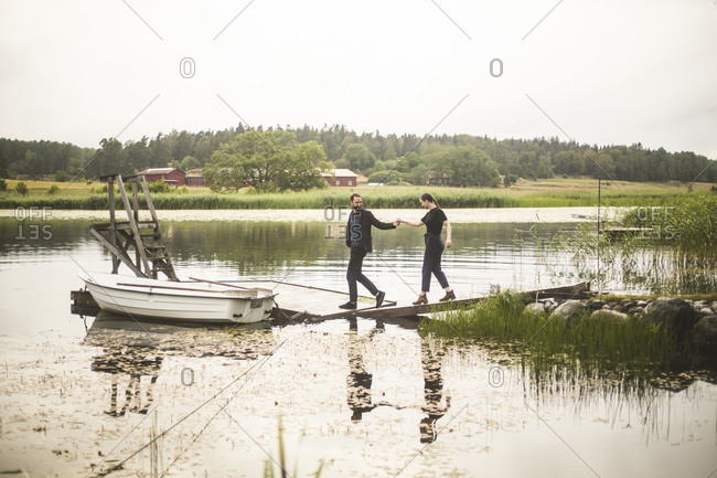 Couple holding hands while walking towards jetty over lake during weekend getaway