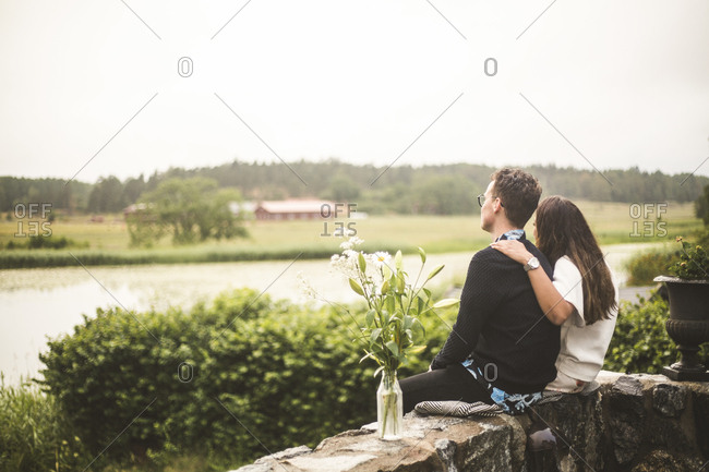 Couple looking at lake while sitting on retaining wall