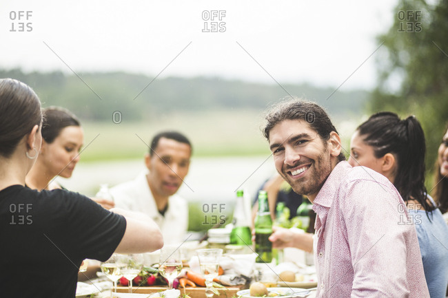 Portrait of smiling young man enjoying dinner with friends at table in backyard