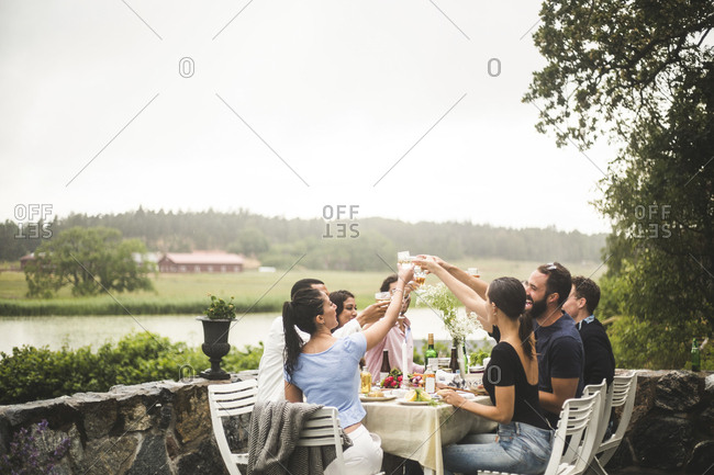 Male and female friends toasting drinks during dinner party in backyard