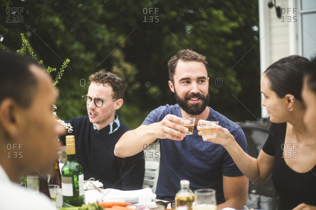 Man and woman toasting drinks while enjoying dinner party with friends in backyard