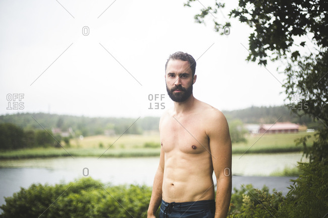 Portrait of confident shirtless man standing in backyard during weekend getaway