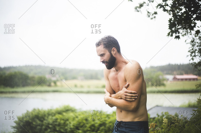 Shirtless mid adult man shivering while standing in backyard during weekend getaway