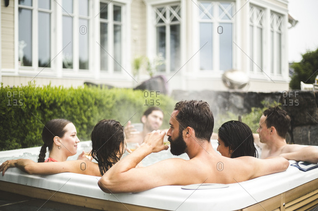Mid adult man drinking alcohol while enjoying with friends in hot tub during weekend