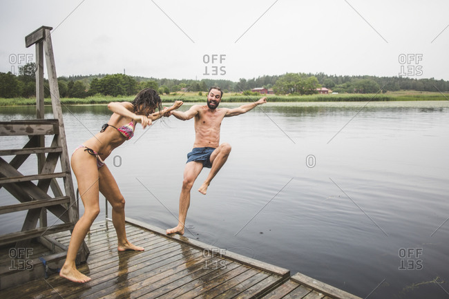 Full length of playful woman pushing male friend in lake while standing on jetty during weekend getaway
