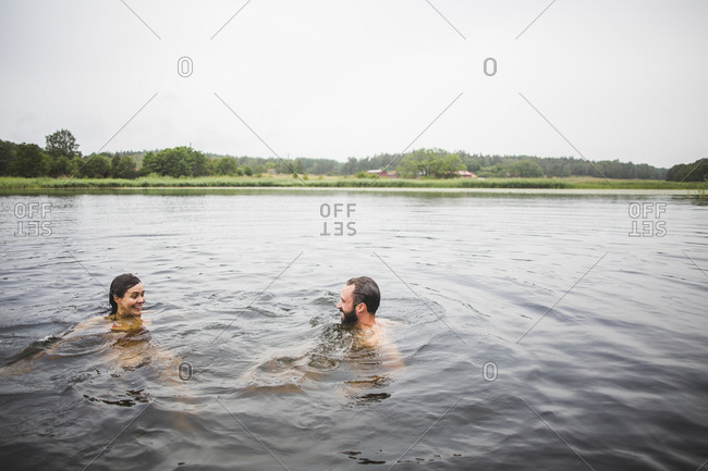 Happy male and female friends swimming in lake against clear sky during weekend