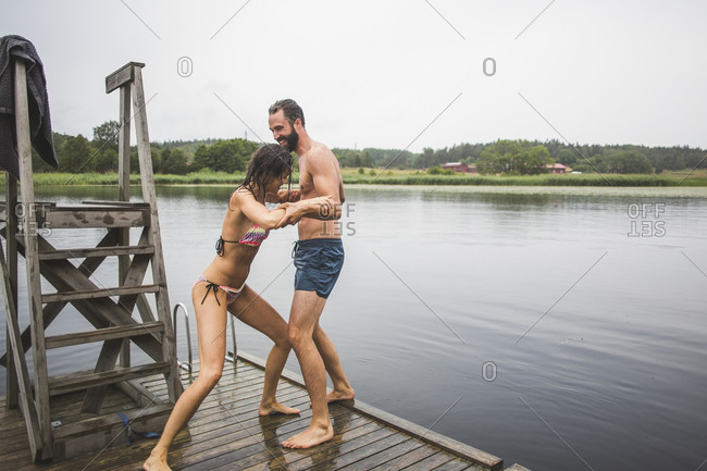Playful woman pushing male friend in lake while standing on jetty during weekend getaway