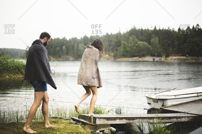 Male and female friends wrapped in towels walking towards jetty over lake during weekend getaway