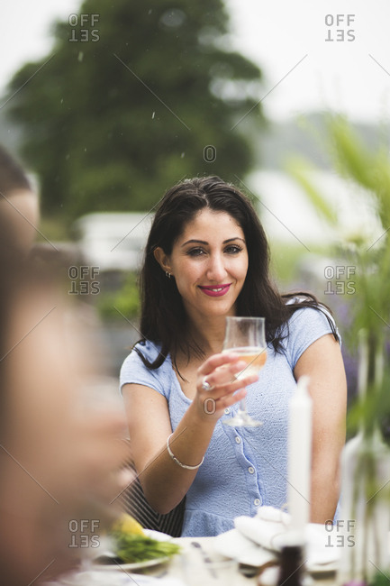 Portrait of smiling young woman holding wineglass at table during dinner party