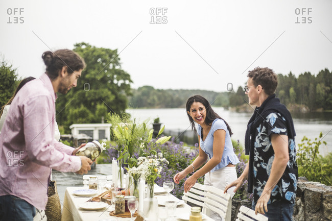 Happy multi-ethnic friends setting table for dinner party in backyard against clear sky
